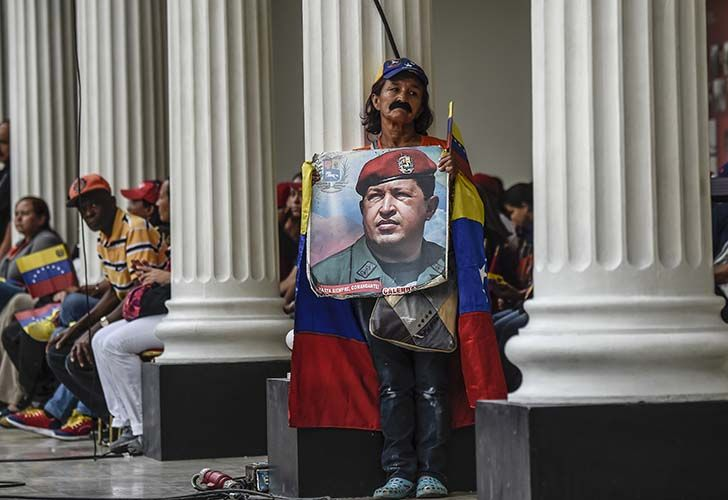 Supporters of Venezuelan president Nicolás Maduro holds a photo of the deceased former president Hugo Chávez outside the National Assembly in Caracas.