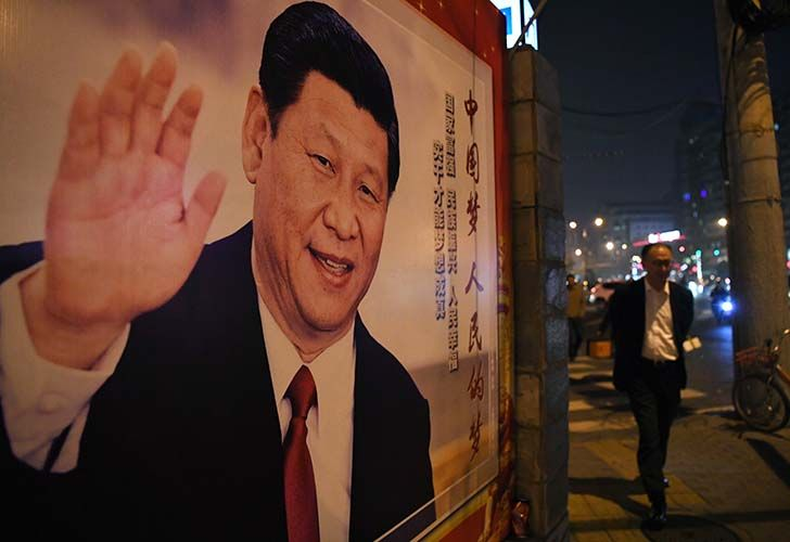 A man walks past a roadside poster of Chinese President Xi Jinping after the closing of the 19th Communist Party Congress in Beijing. Xi Jinping's name was added to the Communist Party's constitution at a defining congress, elevating him alongside Chairman Mao to the pantheon of the country's founding giants.
