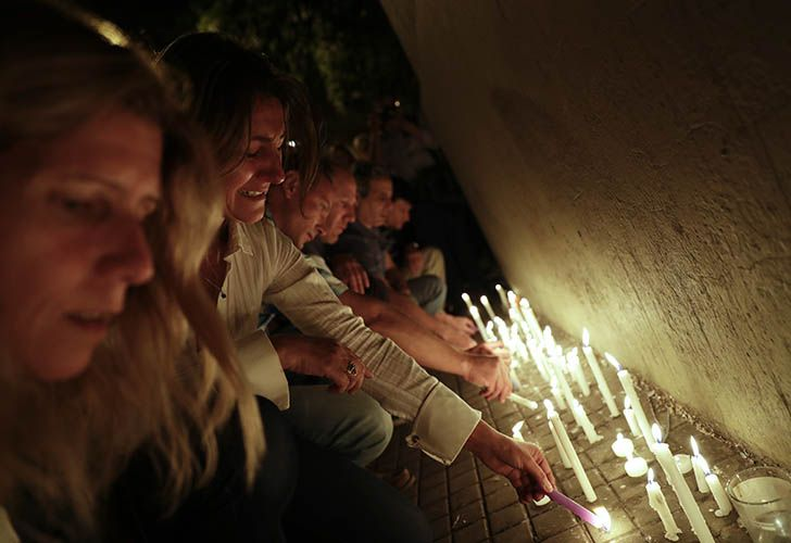 Locals place candles outside the Polytechnic School during a vigil in Rosario. Five victims killed in the bike path attack near the World Trade Center in New York were part of a group of friends celebrating the 30th anniversary of their graduation from the school in Rosario.