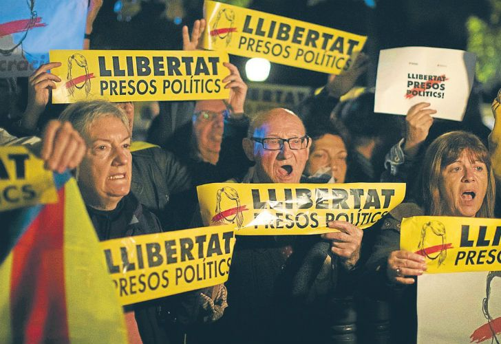 "Demonstrators holding banners reading in Catalan ""Freedom for the political prisoners"" gather outside the Catalonian Parliament to protest against the decision to jail ex-members of the Catalan government."