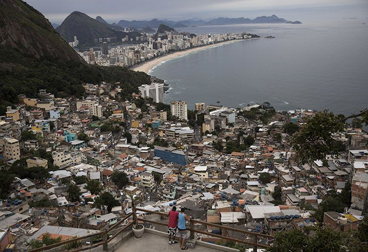 People overlook Rio de Janeiro from the Vidigal slum. Opening the hillside favelas to tourists seemed like a winning idea: they get breathtaking views, the slum residents could cash in, and foreign visitors would see another part of the city, but soaring violence has rekindled a concern about safety.