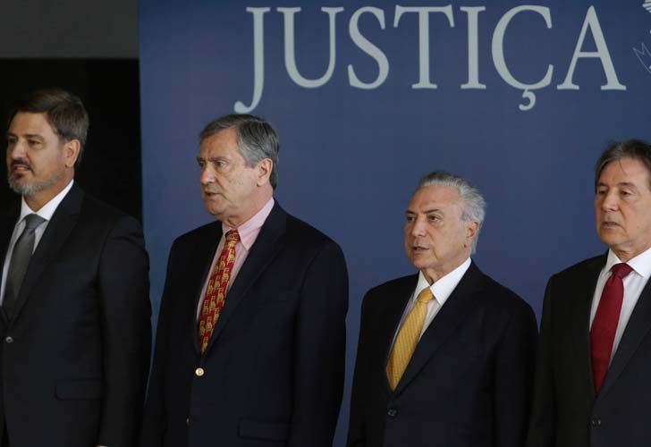 Brazil's President Michel Temer, second from right, accompanied by the President of the Senate Eunicio Oliveira, right, Minister of Justice Torquato Jardim, second from left, and the new Director-General of the Federal Police, Fernando Segovia, left, listen to Brazil's national anthem during Segovia's swearing-in ceremony in Brasilia on Monday.