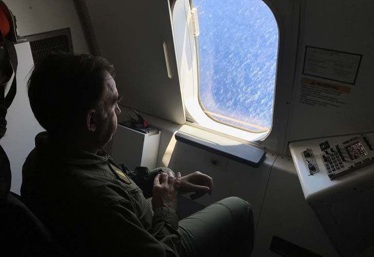 A member of the Argentine Navy looks out the window of a P8-A Poseidon aircraft of the US Navy Patrol and Reconnaissance Wing (CPRW) 11 as it assists the Argentine military in their search for the missing submarine ARA San Juan.