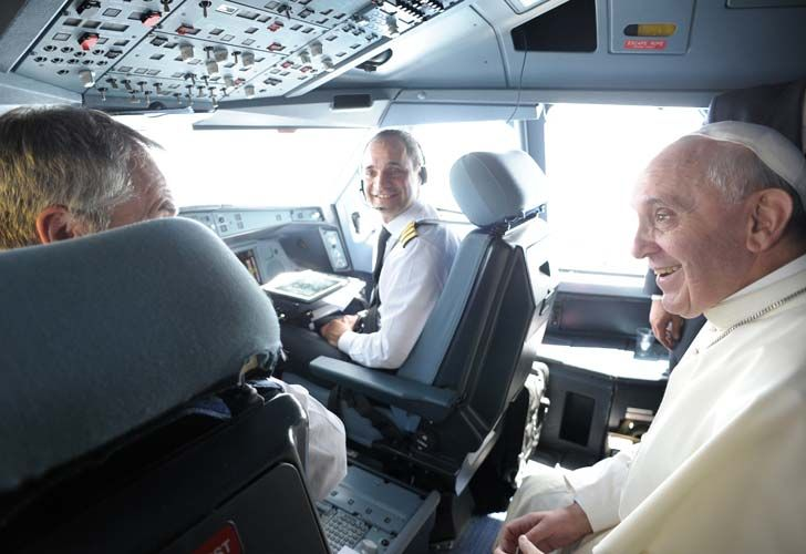 Alberto Colautti (centre) talks with Pope Francis during a recent flight.