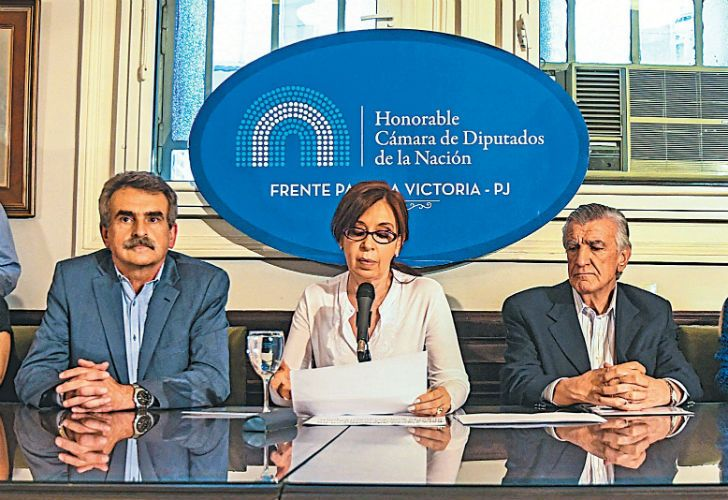 Cristina Fernández de Kirchner, flanked by Victory Front and Peronist lawmkers, delivers a speech at the Congress building to the press.
