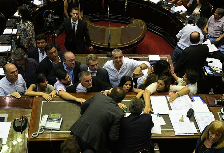 Lawmakers huddle around speaker Emilio Monzó in the middle of a scandalous session of Congress over the ruling Cambiemos coalition's pension reform package.