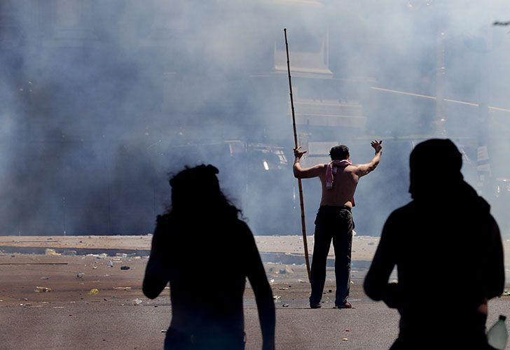 A protester armed with a stick taunts police during clashes in Buenos Aires. Argentine police clashed Thursday with demonstrators protesting reforms to the retirement and pension system.
