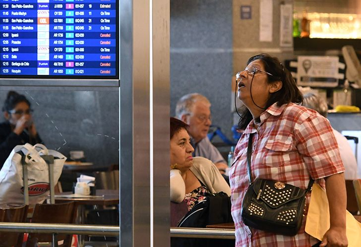 A lady checks the flight status board at Aeroparque airport in Buenos Aires as airlines Latam and Aerolineas Argentinas, adhering to a December 2017 general strike, go about reprogramming flights.