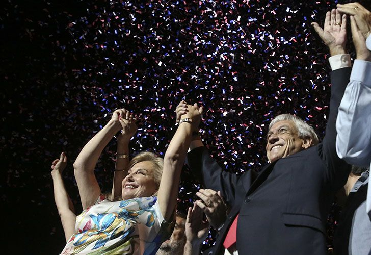 Former president Sebastián Piñera, with his wife Cecilia Morel, stands before supporters as he celebrates winning the presidential election run-off in Santiago on Sunday night.
