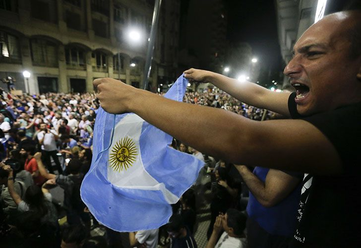 A demonstrator waves an Argentine flag as a crowd marches to the Congress to protest against a pension reform in the capital.