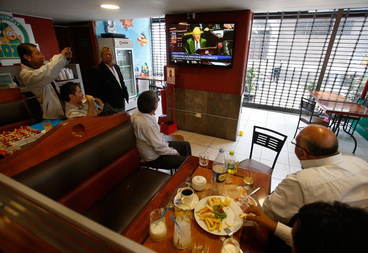 Customers eat breakfast in a restaurant as they watch Peru's President Pedro Pablo Kuczynski on a TV screen in Lima, Peru, Thursday, Dec. 21, 2017. Kuczynski is facing an impeachment vote following revelations that his private consulting business received money from the Brazilian construction company implicated in Latin America's biggest corruption scandal. (AP Photo/Karel Navarro)