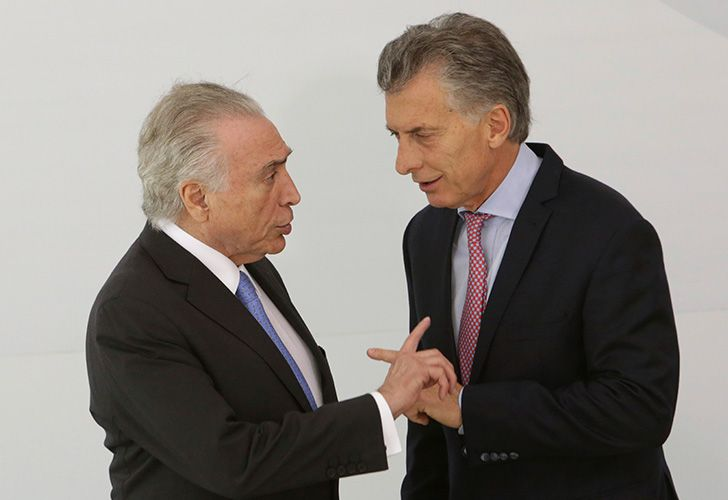 Brazil's President Michel Temer, left, talks with Argentine President Mauricio Macri, before the official photo of the 2017 Mercosur and Associated States Summit of Heads of State.