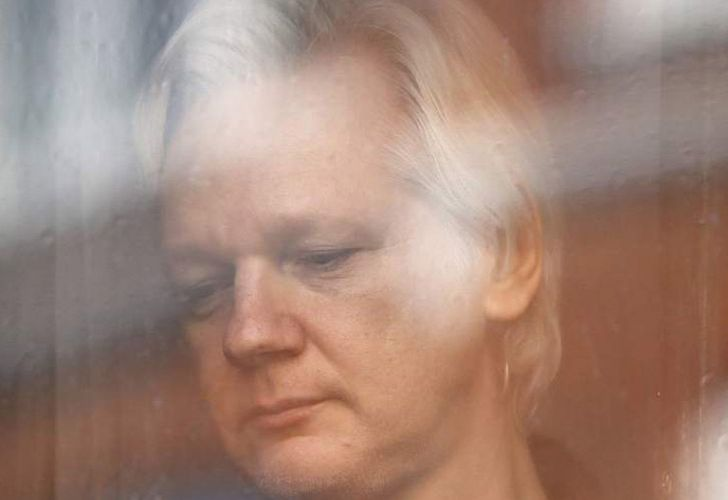 Julian Assange looks out the window from the Ecuadorean embassy in London in this file photograph.