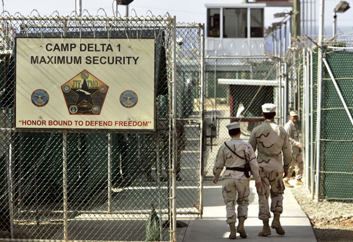 In this June 27, 2006 file photo, reviewed by a U.S. Department of Defense official, U.S. military guards walk within Camp Delta military-run prison, at the Guantanamo Bay US Naval Base, Cuba.