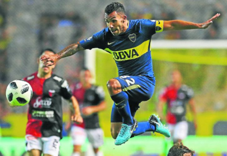 Boca Juniors forward Carlos Tevez jumps over a strong challenge from Atlético Colón defender Germán Conti (right), during their Superliga clash at La Bombonera last weekend.