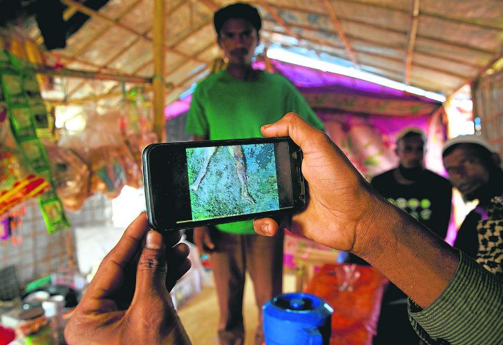 Rohingya Muslim refugee Mohammad Karim, 26, shows a mobile phone video of Gu Dar Pyin's massacre inside his kiosk at the Kutupalong refugee camp, in Bangladesh. On September 9, a villager from Gu Dar Pyin captured three videos of mass graves, time-stamped between 10.12am and 10.14am, when he said soldiers chased him away.
