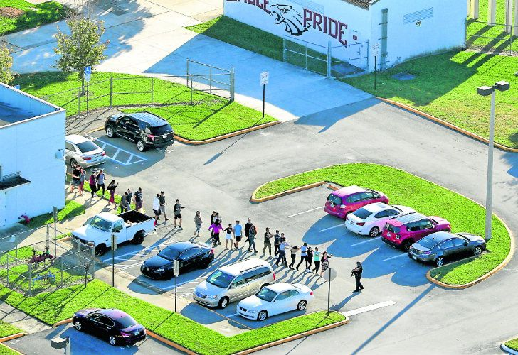 Students are evacuated by police from Marjory Stoneman Douglas High School in Parkland, Florida, after a shooter opened fire on the campus.