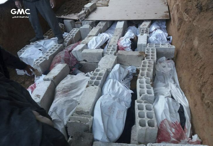 The bodies of Syrians killed during airstrikes and shelling by Syrian government forces in recent days, buried in a mass grave in Ghouta, a suburb of Damascus.