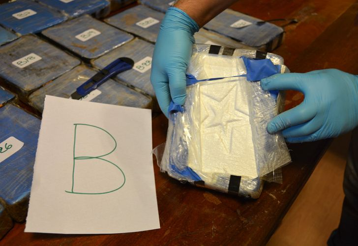 In this photo taken on December 14, 2016, released yesterday by the Security Ministry, a police officer shows a package of cocaine that with a star sign, that was found in an annex building of the Russian Embassy in Buenos Aires. A Russian diplomatic official and an Argentine police officer are among those arrested after authorities seized the cocaine shipment of 389 kilogrammes at the Embassy that prompted them to launch a yearlong joint investigation to dismantle a drug ring, the government said.