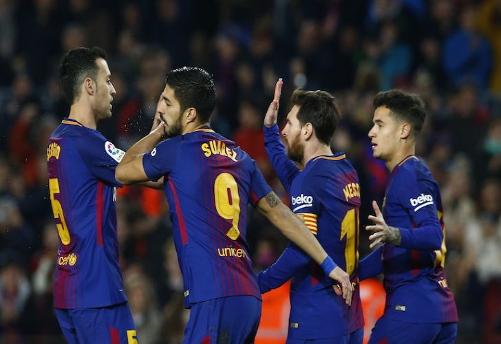 Barcelona players (left to right) Sergio Busquets, Luis Suárez, Lionel Messi and Philippe Coutinho celebrate after Suárez scores against Girona on Saturday.