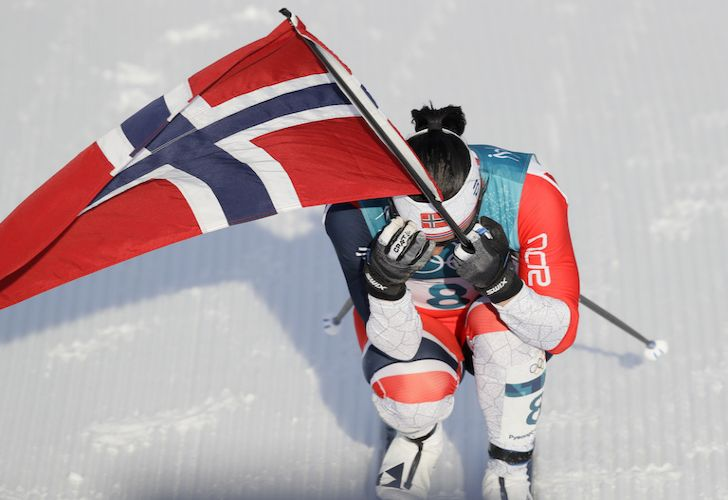 Norway's Marit Bjoergen carries her country's flag after winning gold in the women's 30k cross-country skiing competition at the 2018 Winter Olympics