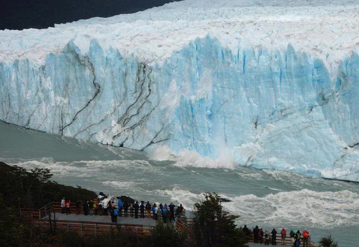 Tourists watch pieces of ice falling from the Perito Moreno glacier, at Parque Nacional Los Glaciares near El Calafate, in the province of Santa Cruz, on March 12, 2018.