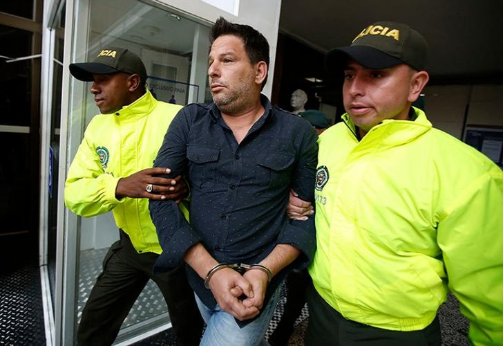Police escort Cuban suspect Raul Gutierrez to court where a judge will rule on prosecutors' request he be held on terrorism and conspiracy charges in Bogota, Colombia.