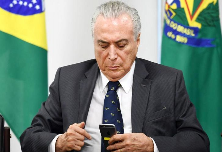 Brazilian President Michel Temer looks at a mobile phone, at the Planalto Palace in Brasilia.