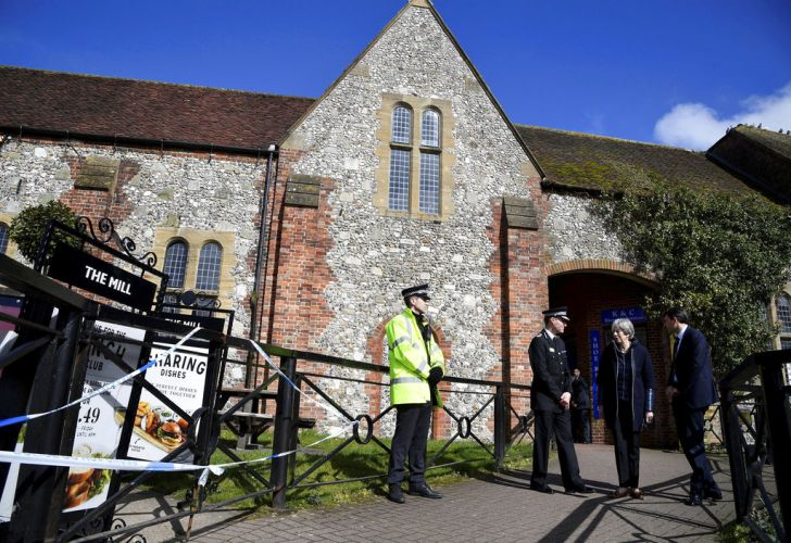 British Prime Minister Theresa may examines the area where former Russian double agent Sergei Skripal and his daughter were found critically ill outside The Mill pub in Salisbury, England on Thursday.