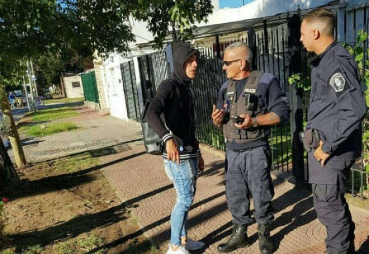 Racing midfielder Ricardo Centurión talks with police officers after running a red light in Lanús on Monday morning.