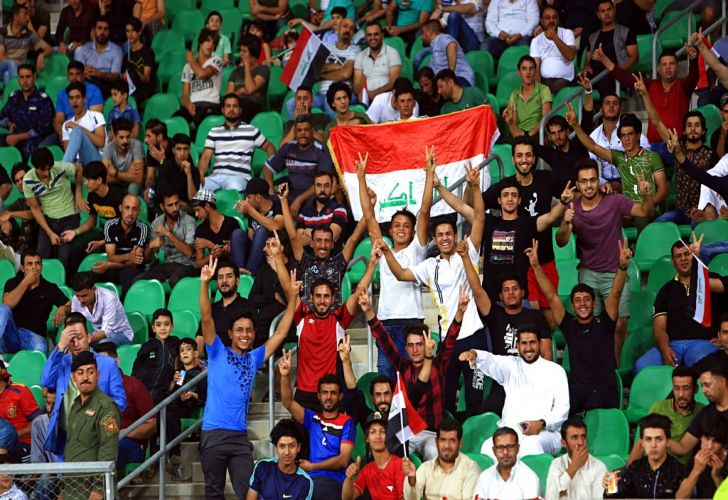 Iraqi football fans display national flags as they cheer during a friendly between Kenya and Iraq in Basra, Iraq last October.