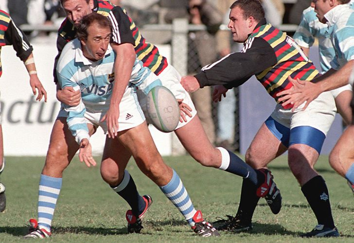 In this file photo taken on April 17, 1999, former rugby player Hugo Porta (centre) from Argentina reaches for the ball as Berrie-Jon Mather tackles him, in Buenos Aires, during a friendly match between the Argentine