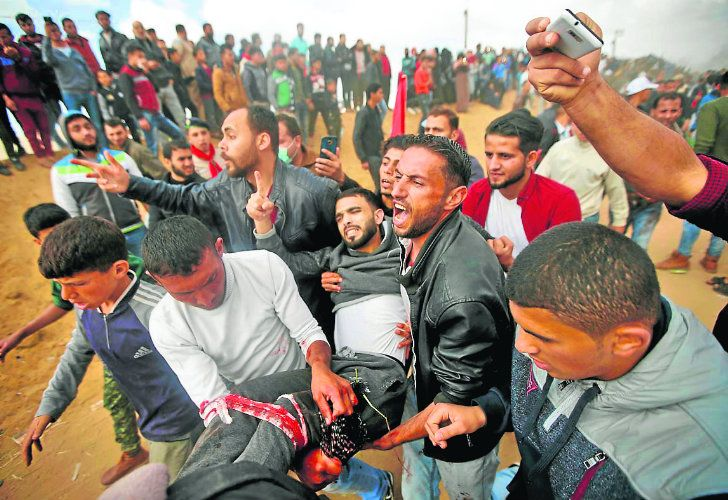 Palestinian protesters evacuate a wounded youth during clashes with Israeli troops along the Gaza Strip border with Israel, east of Khan Younis, Gaza Strip, yesterday.