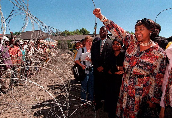 Winnie Madikizela-Mandela, former wife of Nelson Mandela, greets demonstrators, behind razor wire at a bail hearing for businessman Piet Odendaal in Viljoenskroon, South Africa in November 2000.