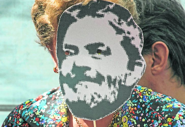 Former Brazil president Dilma Rousseff wears a mask with the face of jailed PT leader Luiz Inácio Lula da Silva.