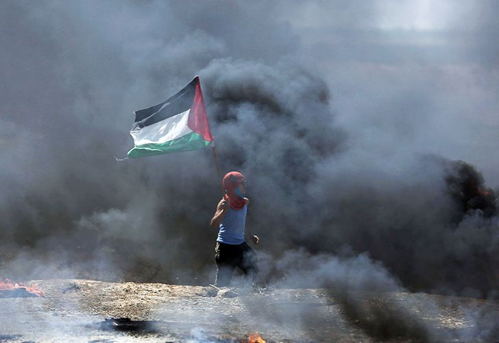 A boy waves a Palestinian flag while walking through black smoke from burning tires during a protest on the Gaza Strip's border with Israel, Monday, May 14, 2018. Thousands of Palestinians are protesting near Gaza's border with Israel, as Israel prepared for the festive inauguration of a new US Embassy in contested Jerusalem.