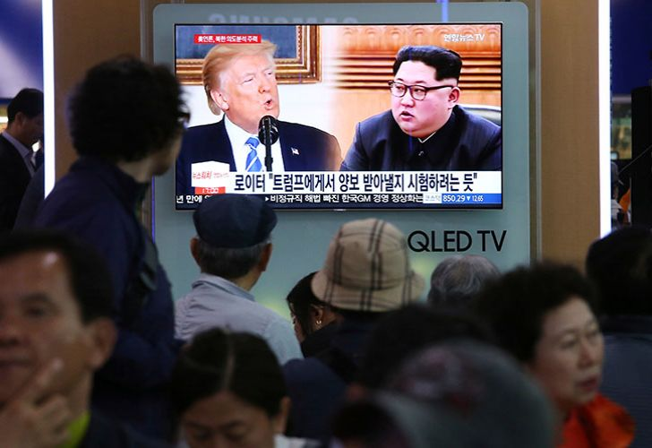 People watch a TV screen showing file footage of US President Donald Trump, left, and North Korean leader Kim Jong Un during a news program at the Seoul Railway Station in Seoul, South Korea, Wednesday, May 16, 2018.