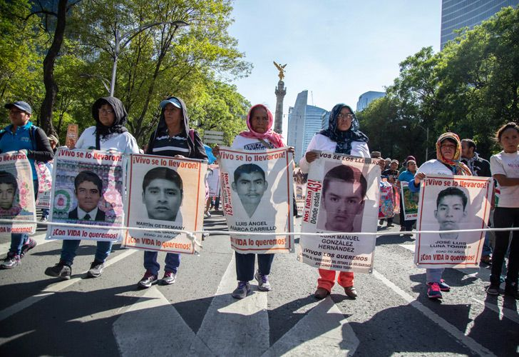 In this May 26, 2018 file photo, people display the faces of the 43 missing students during a protest to raise awareness of the students who went missing nearly four years ago, in Mexico City. The rural college students mysteriously vanished on September 26, 2014 in Iguala when they were interrupted on their way to demonstration by police. On June 4, 2018, a federal court in Mexico ordered that the investigation into the 2014 disappearance of 43 college students be done again under the supervision of a truth commission.