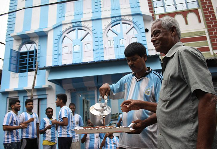 Shib Shankar Patra (second right), Argentina football fan, serves tea to fans and customers in front of his apartment painted in blue-and-white, ahead of the upcoming 2018 World Cup.