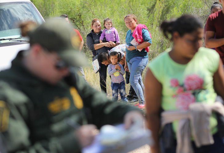 Central American asylum seekers wait as US Border Patrol agents take them into custody, on June 12, 2018 near McAllen, Texas.