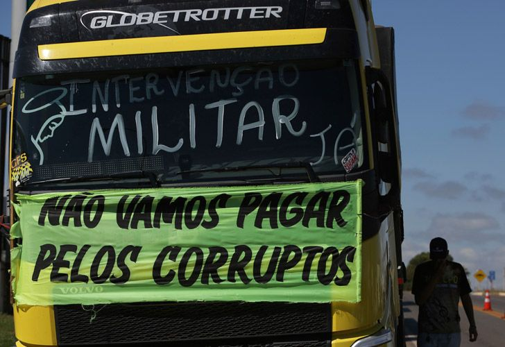 A striking trucker protests rising fuel costs as he walks beside a truck with a sign that reads in Portuguese: