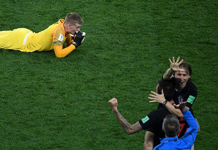 England's goalkeeper Jordan Pickford reacts after losing the Russia 2018 World Cup semi-final football match between Croatia and England at the Luzhniki Stadium in Moscow, while Croatia captain Luka Modric leads the celebrations.