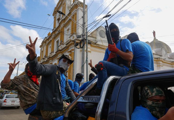 Armed pro-government militia members flash victory signs as they occupy the Monimbo neighbourhood of Masaya, Nicaragua. On Tuesday, Nicaraguan government forces retook the symbolically important neighbourhood that had become a centre of resistance to Nicaraguan President Daniel Ortega's government.