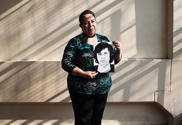 Fifty-four-year-old teacher Vittoria E Natto poses for a portrait inside her high school holding a photo of herself when she was nine years old, in Santiago, Chile. Forty-five years after the Chilean coup led by General Augusto Pinochet, there are still stories to tell of the horrors that followed the September 11, 1973, overthrow of president Salvador Allende. That repression is still stamped on the mind of Natto, who uses a pseudonym to write and speak about her history.