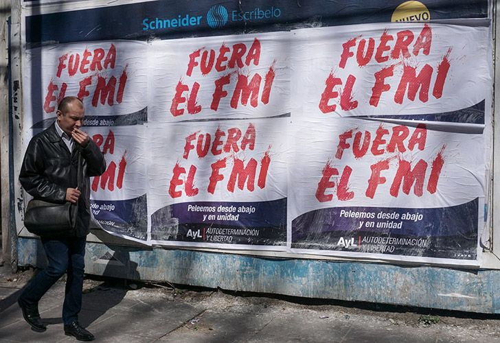 A man walks past posters rejecting the government's negotiations with the International Monetary Fund in Buenos Aires.