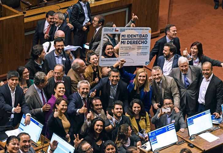 Chilean deputies celebrate as they hold a giant fake Chilean Identity card reading