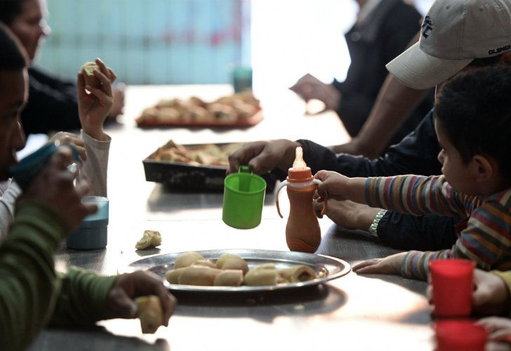 People have a snack at Los Piletones soup kitchen, run by social activists in the Villa Soldati neighbourhood of Buenos Aires.