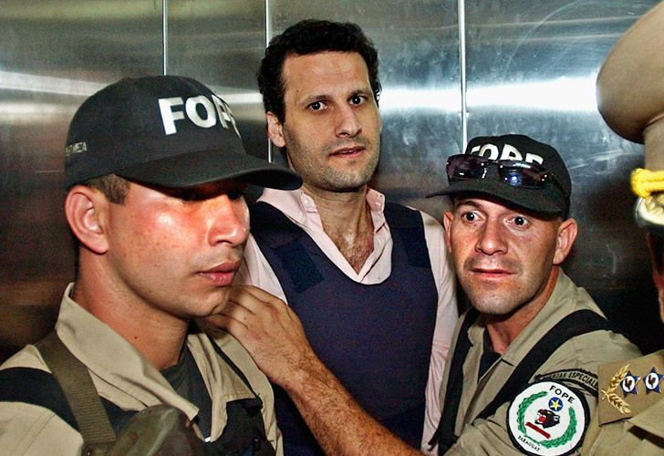 In this November 2003 file photo, Lebanese citizen Assad Ahmad Barakat, who was then facing tax evasion charges, is escorted by police to a courthouse in Asunción, Paraguay.