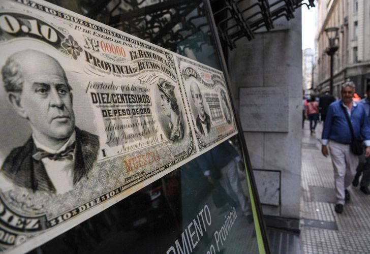 People walk past a bank's branch decorated with images of old peso bills in Buenos Aires.