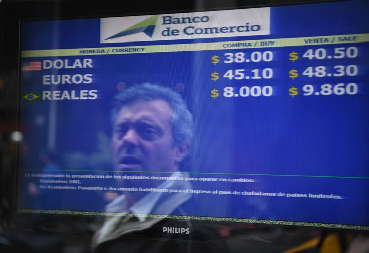 A passerby is reflected in the buy-sell board of a bureau de exchange in Buenos Aires.